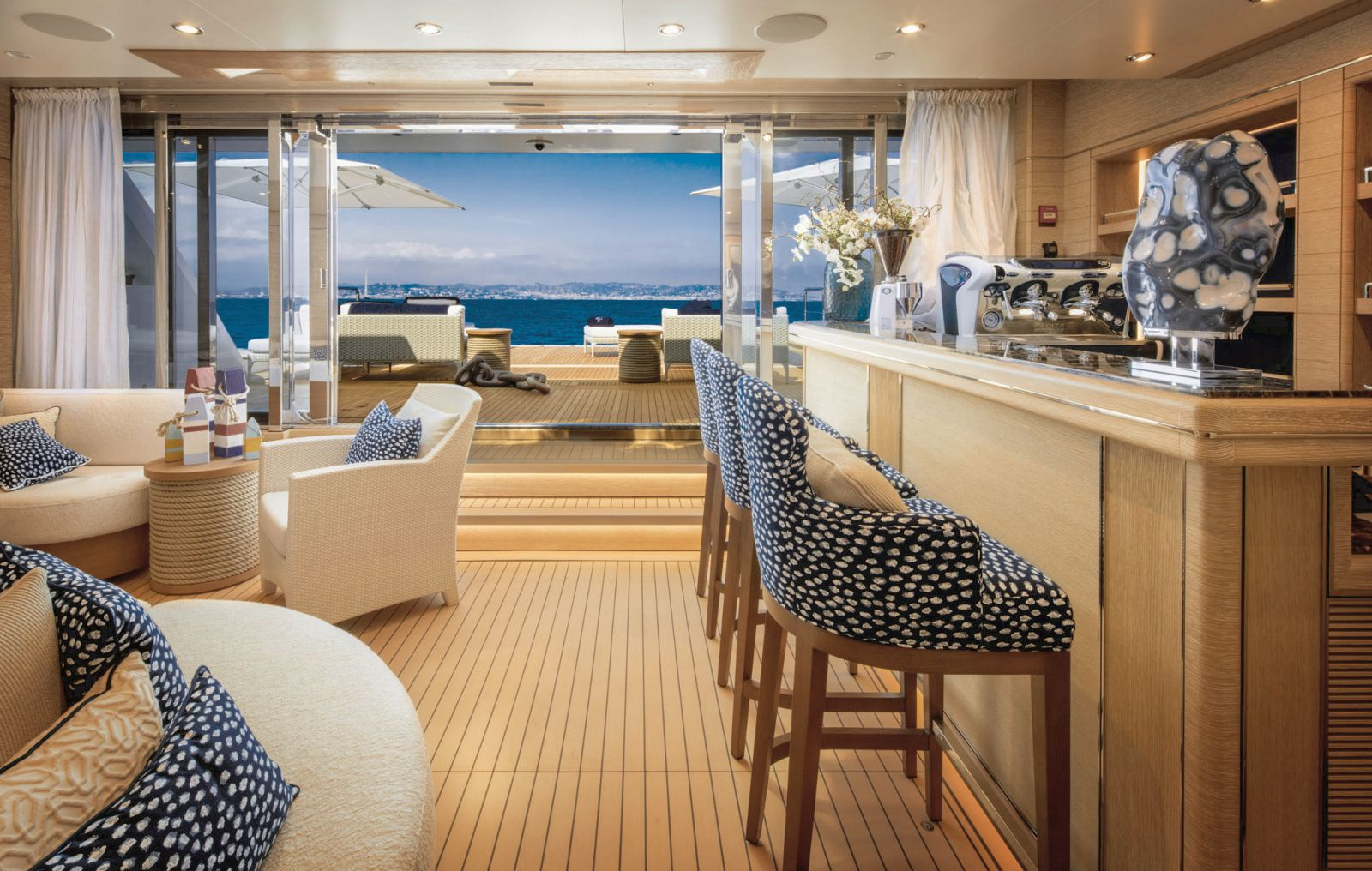 Salon bar and seating area with opened doors looking out to the aft deck. >