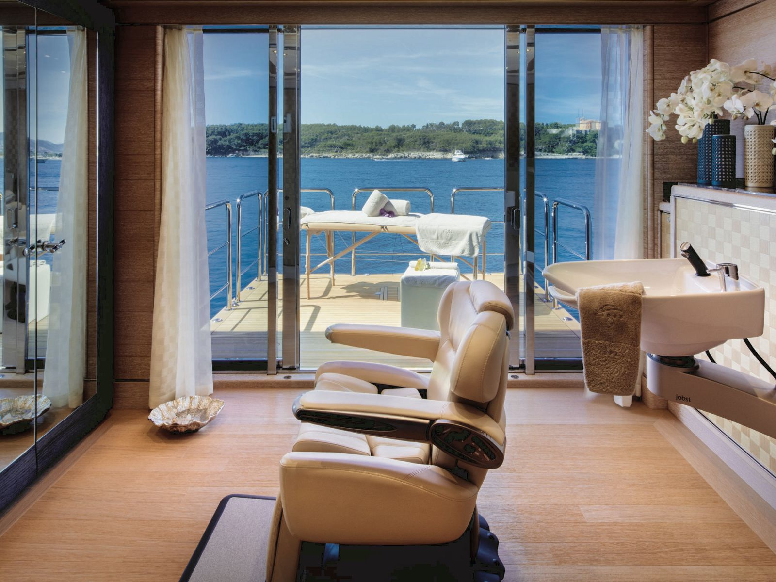 Inetrior spa chair and sink with massage table on the balcony overlooking the water. >