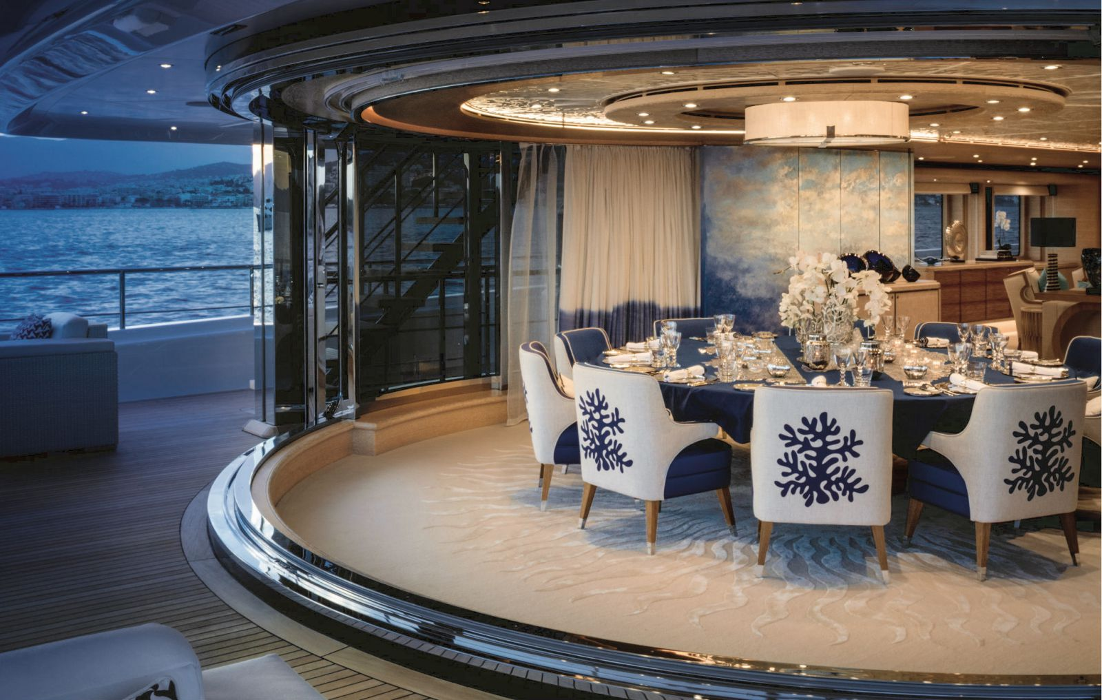 Interior image of the main salong dining area from the aft deck at night. >