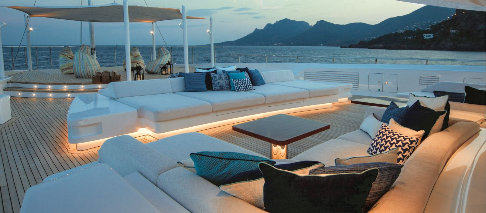 Bow of the boat lit up around the deck couches and overhead coverage. >