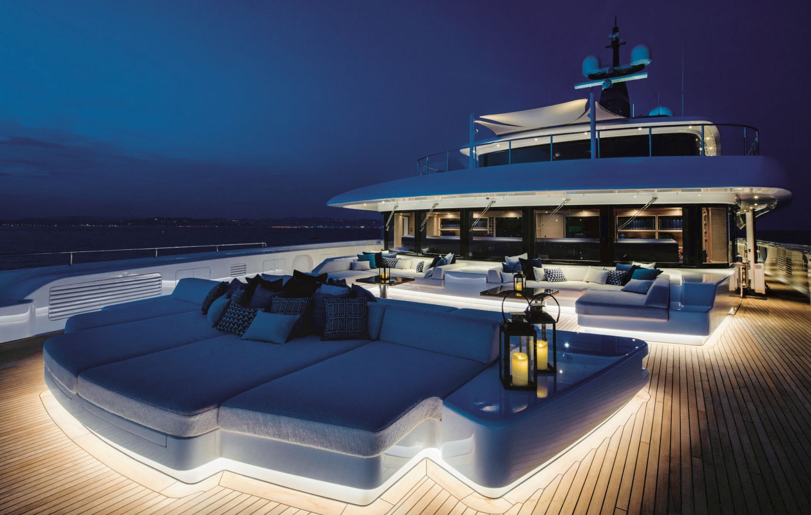 Exterior of the bow at night with the deck lights lighting up the lounging aera. >